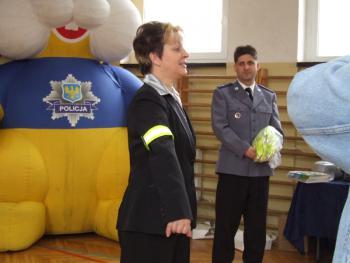 Pani dyrektor Renata Smolińska prezentuje , jak należy nosić opaskę odblaskową